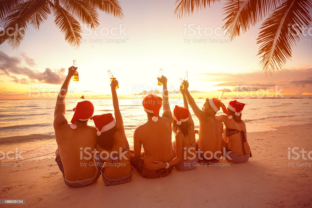 Back view of people with Santa hats sitting on beach stock photo