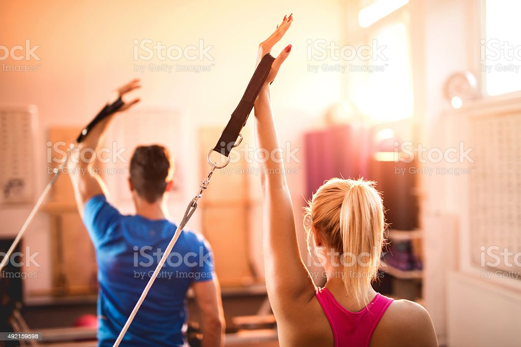 Back view of Pilates reformers exercising in a health club. stock photo