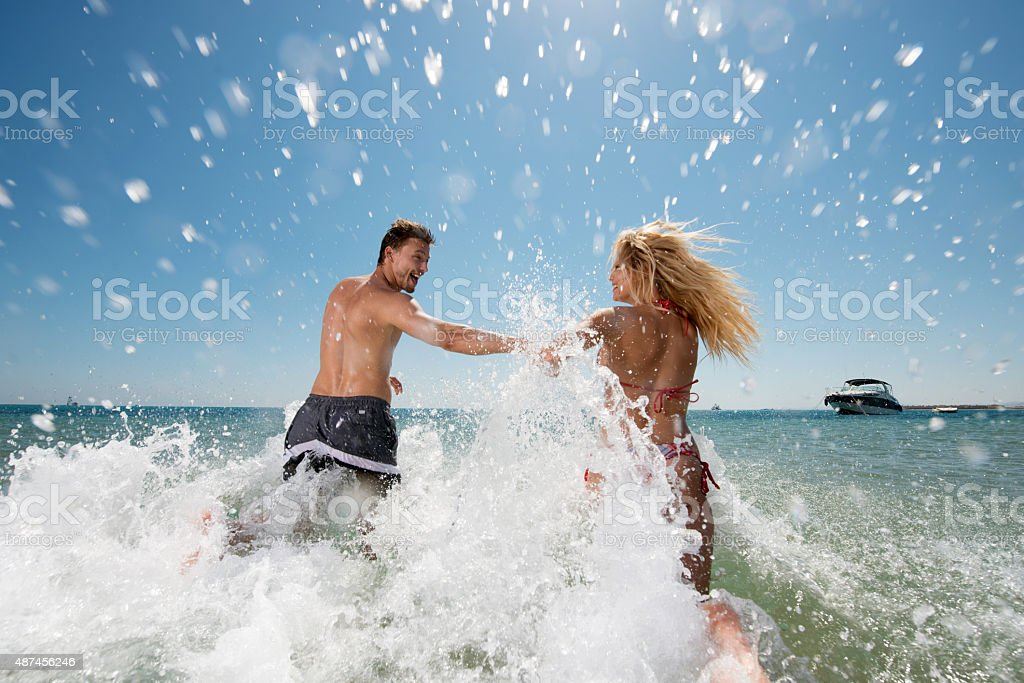 Back view of playful couple running into the sea. stock photo