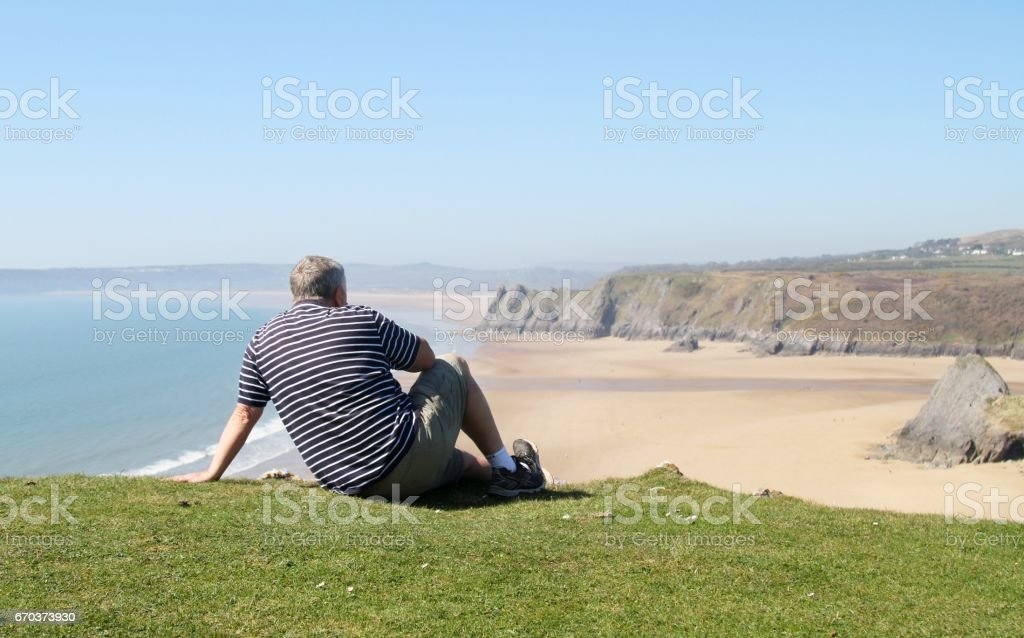 back view of senior man on cliff top stock photo