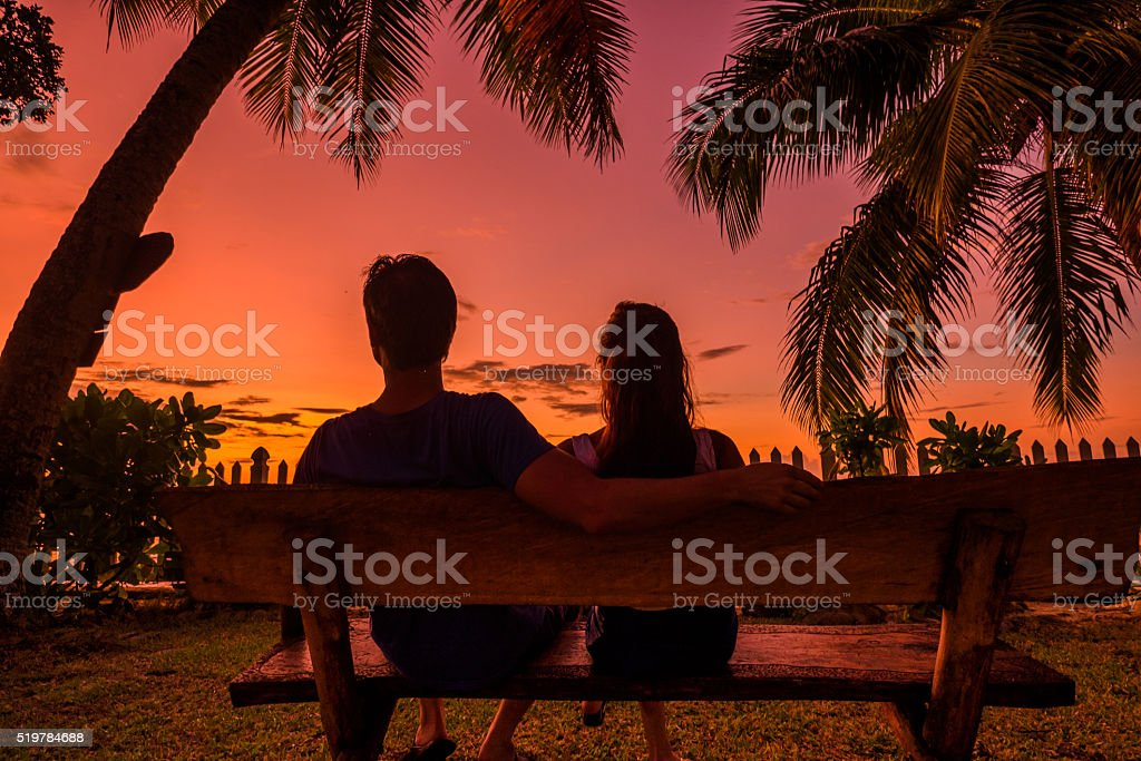 back view of shilouete couple siting on the bench stock photo