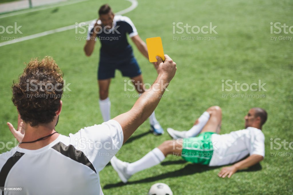 back view of soccer referee showing yellow card to players during game stock photo