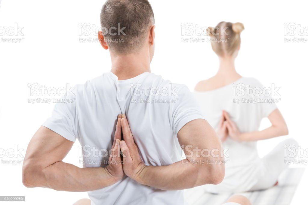 Back view of sporty young people sitting in lotus position with namaste mudra sign stock photo