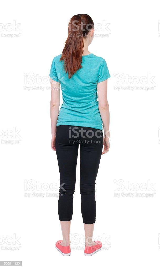 back view of standing young beautiful  woman. girl  watching. stock photo