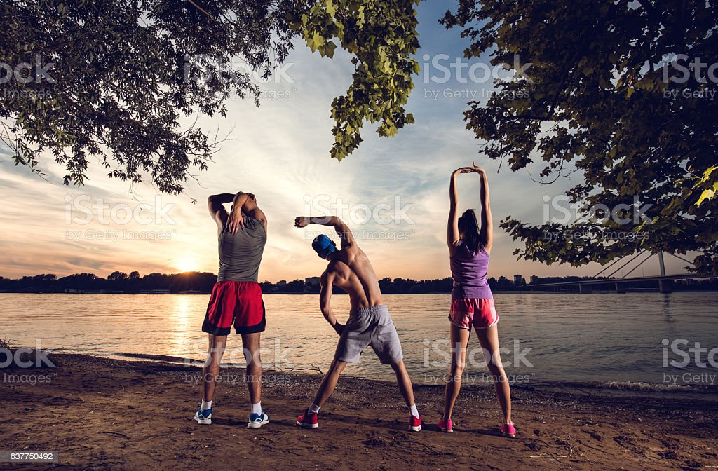 Back view of three athletes stretching at sunset by river. stock photo