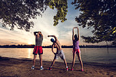 Back view of three athletes stretching at sunset by river.