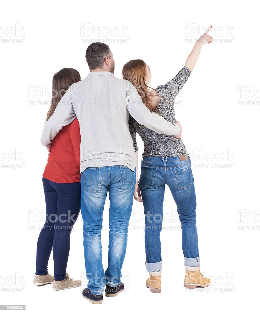 Back view of three friends pointing. stock photo