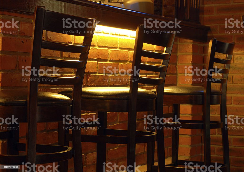 Back view of three illuminated high backed bar stools stock photo