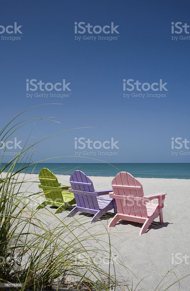 Back view of three pastel colored beach chairs on sand royalty-free stock photo
