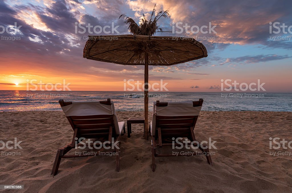 Back View Of Two Deckchairs, Sun Loungers On Sand Beach. stock photo