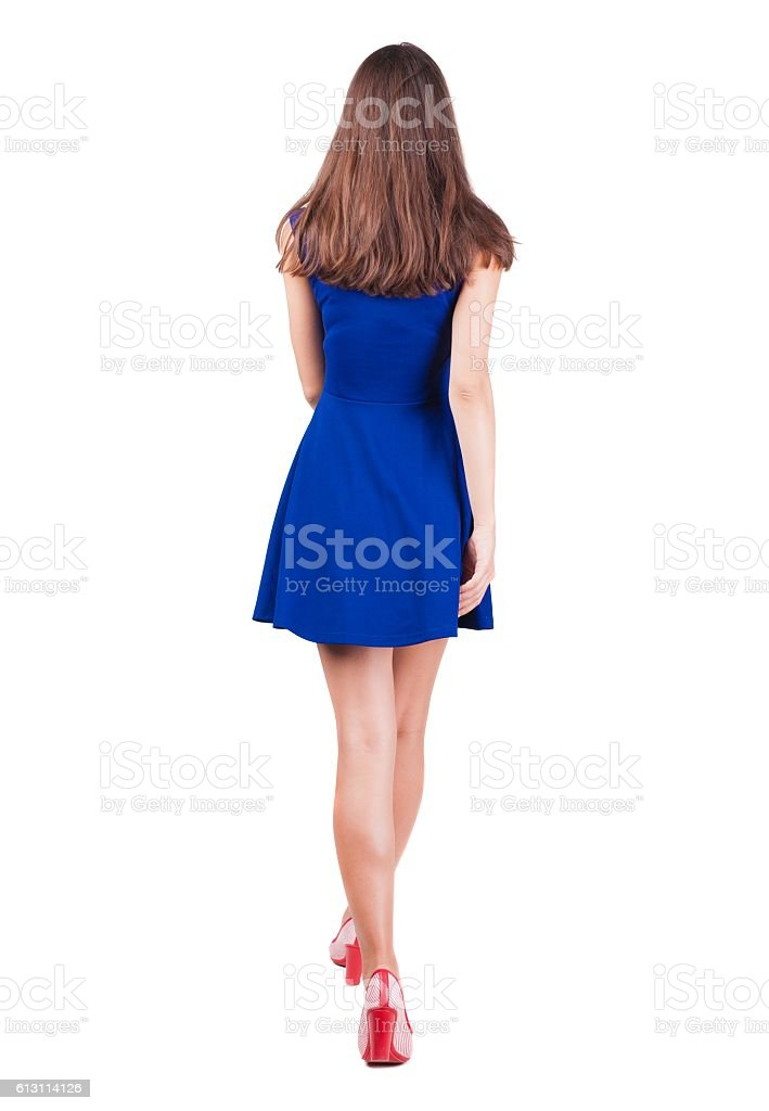 back view of walking woman in dress stock photo