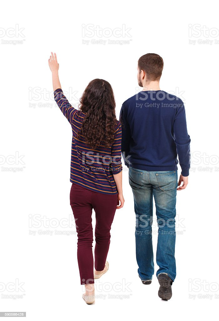 Back view of walking young couple man and woman pointing. stock photo