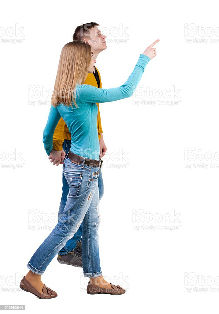 Back view of walking young couple (man and woman) pointing. stock photo