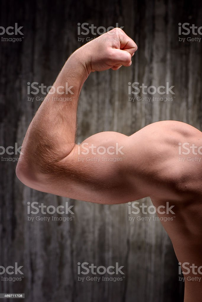 Back view of well formed man demonstrating biceps stock photo