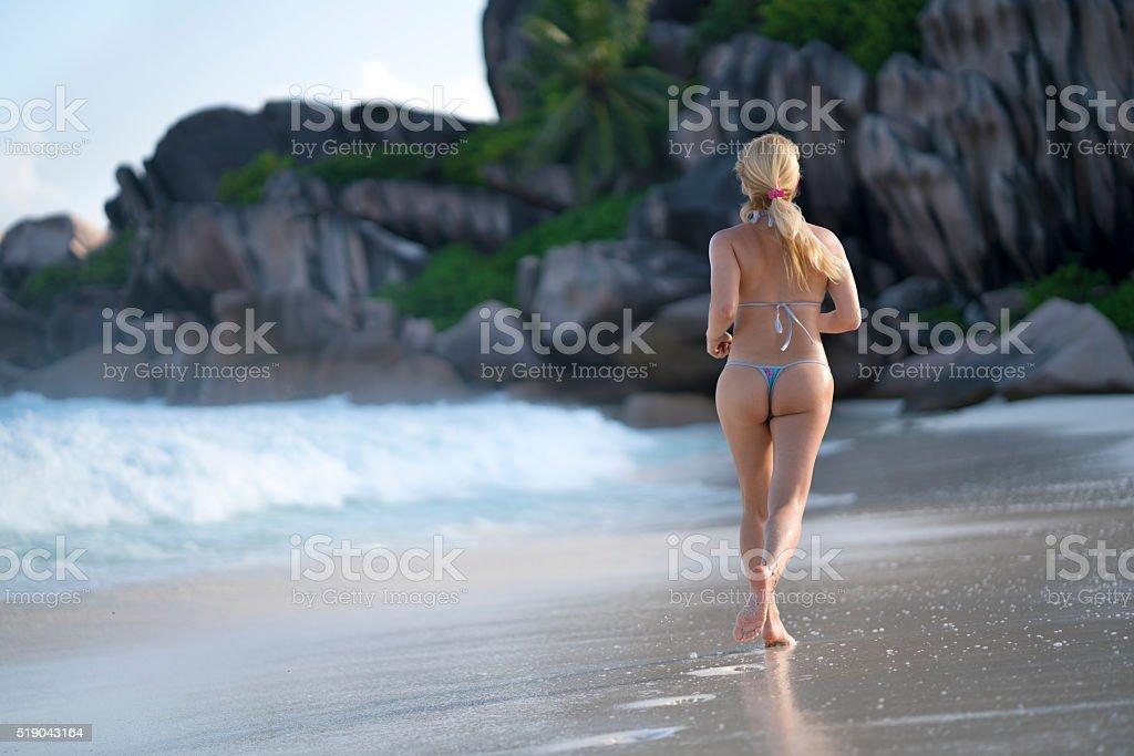Back view of woman in bikini running on the beach. stock photo