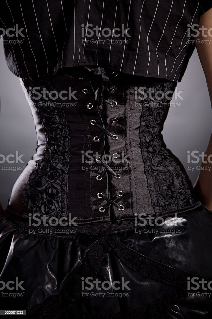 Back view of woman in black rose corset stock photo