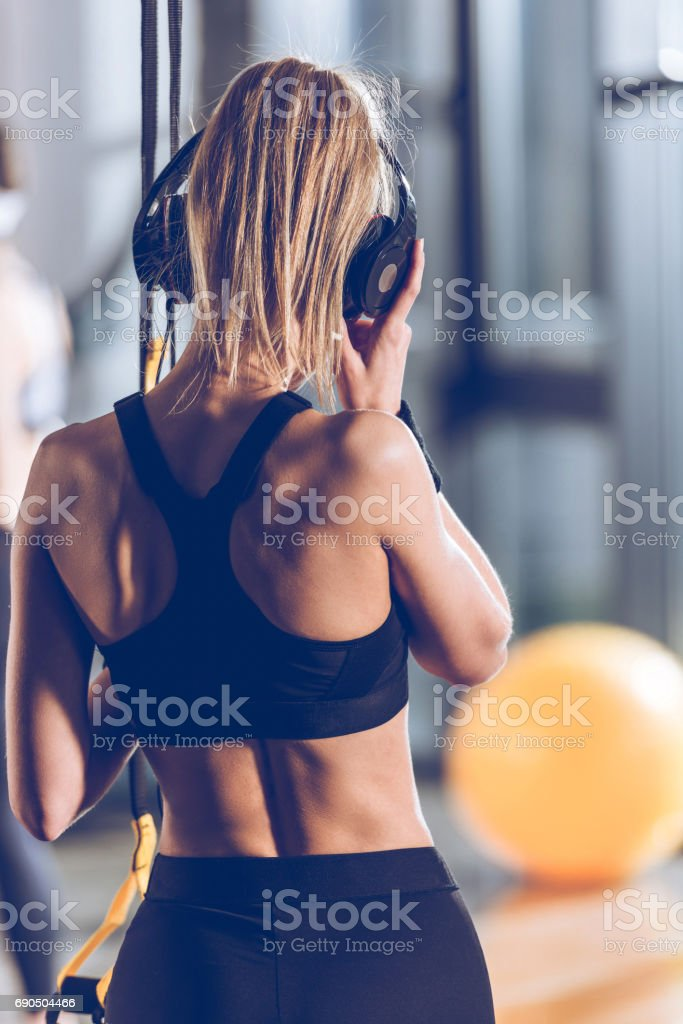 back view of woman listening music in headphones near trx equipment in gym stock photo
