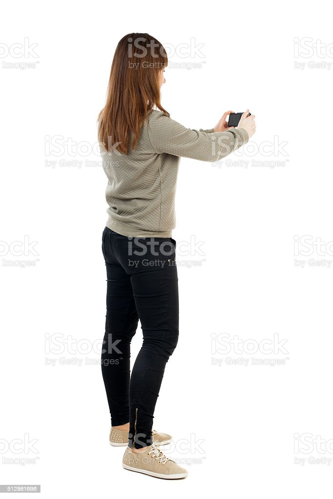Back view of woman photographing. stock photo