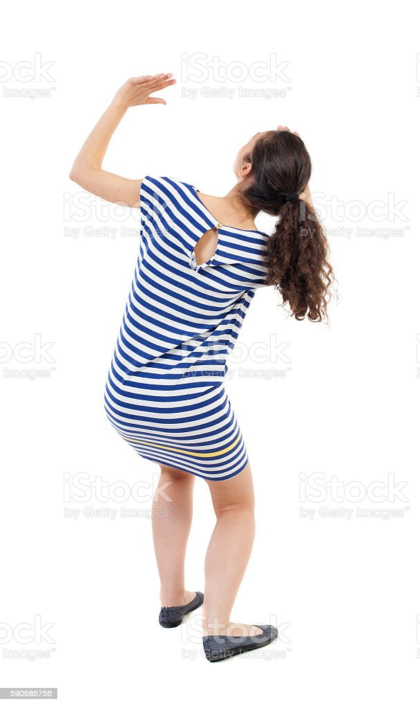 back view of woman protects hands from what is falling stock photo