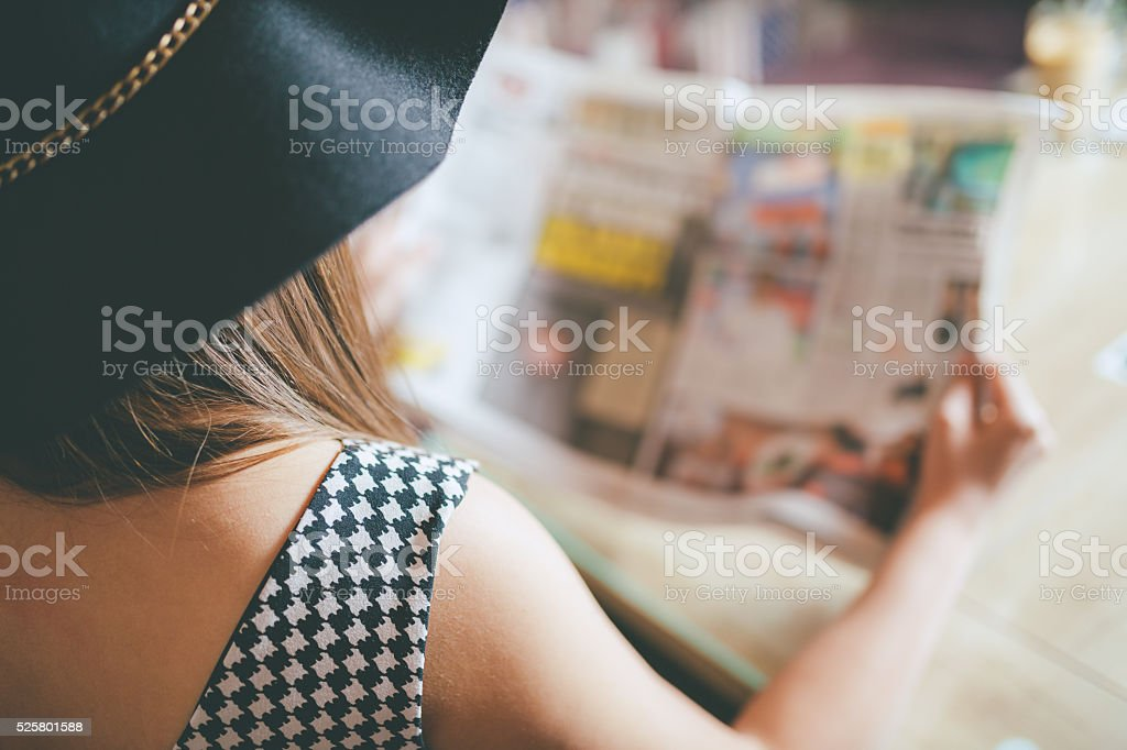 back view of woman reading a newspaper stock photo