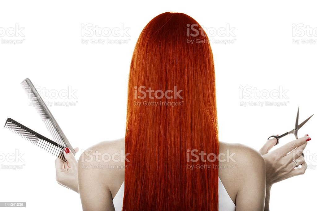 Back view of woman with long red hair with combs & scissors stock photo