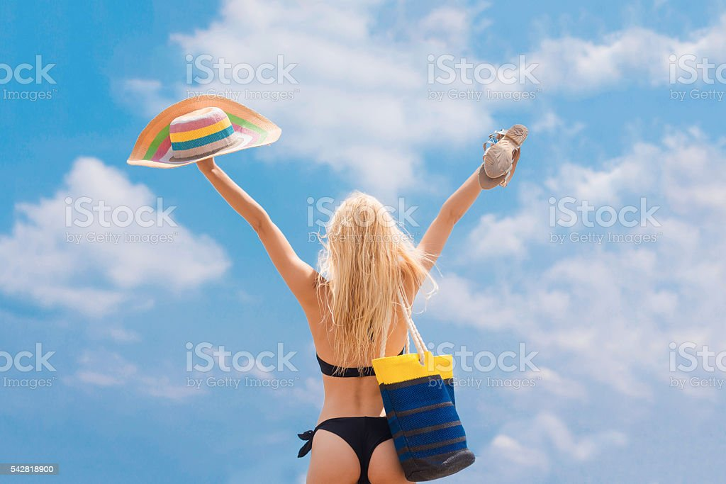 back view of woman with stripy bag and straw hat stock photo