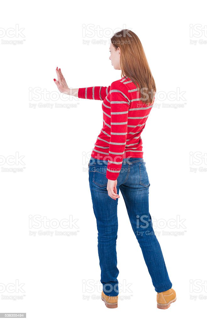 back view of woman. Young woman presses down on something. stock photo