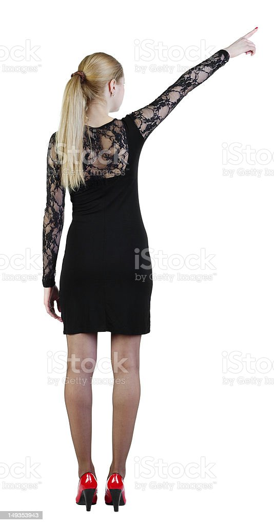 Back view of young blonde woman pointing at wall royalty-free stock photo