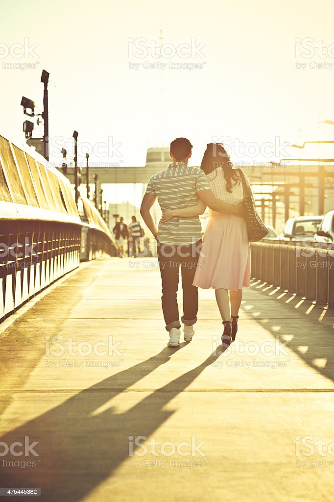 Back view of young couple in the city at sunset stock photo