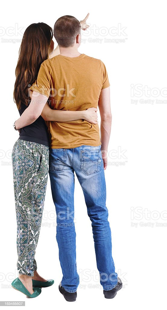 Back view of young couple pointing at wall. royalty-free stock photo