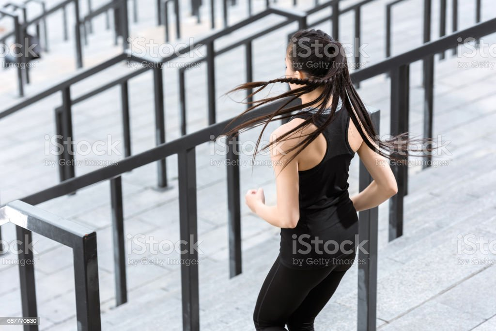 Back view of young fitness woman in sportswear exercising on stadium stairs stock photo
