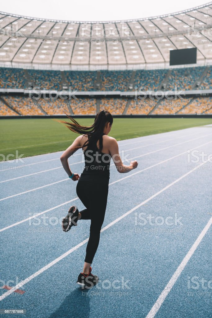 Back view of young fitness woman in sportswear sprinting on running track stadium stock photo