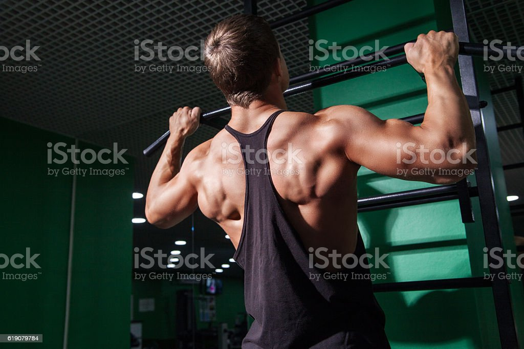 Back view of young man doing pull ups stock photo
