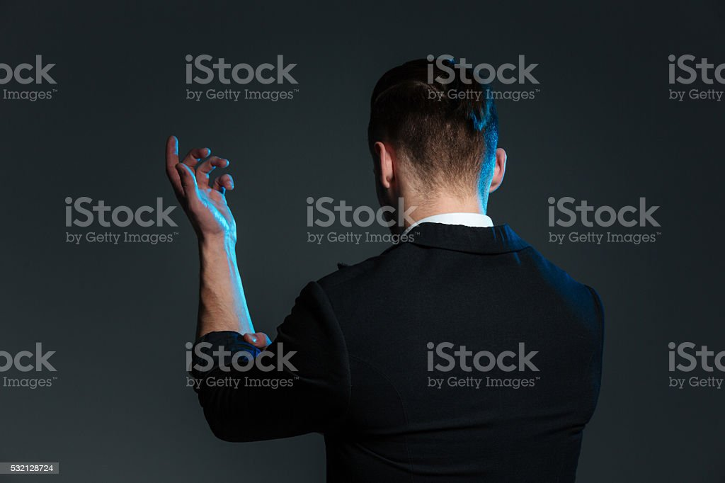 Back view of young man magician standing with raised hand stock photo