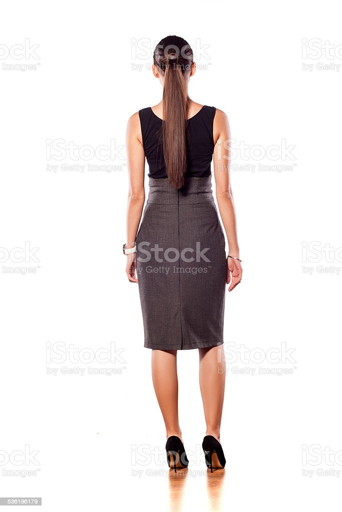 Back view of young woman standing on a white background stock photo