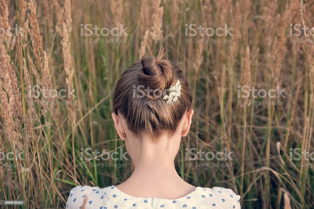Back view of young woman with hair bun stock photo