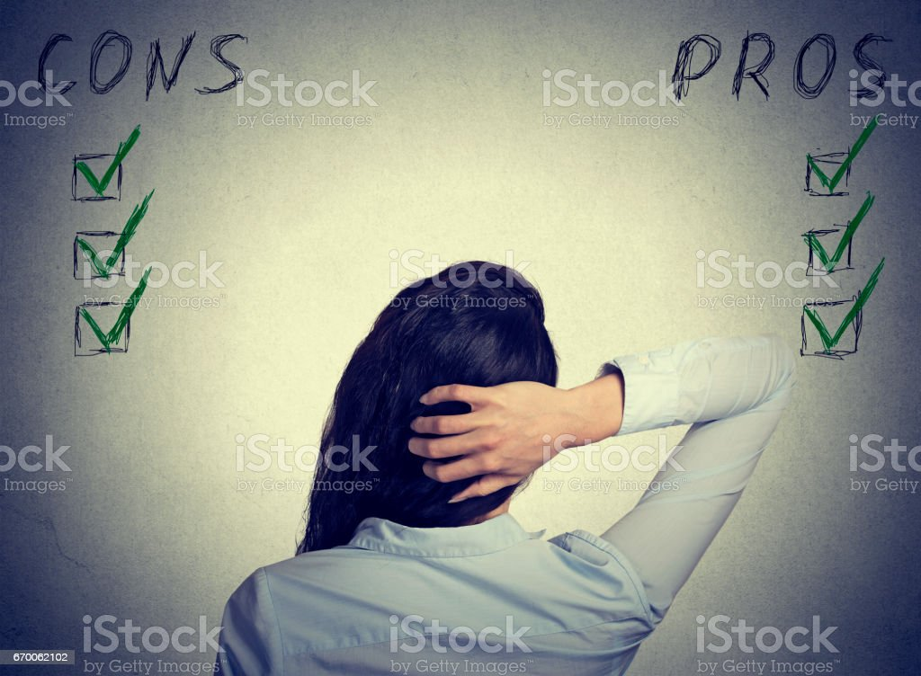 Back view woman making risk research assessment standing at wall with pros and cons stock photo