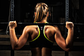 Back view young adult girl doing barbell squats