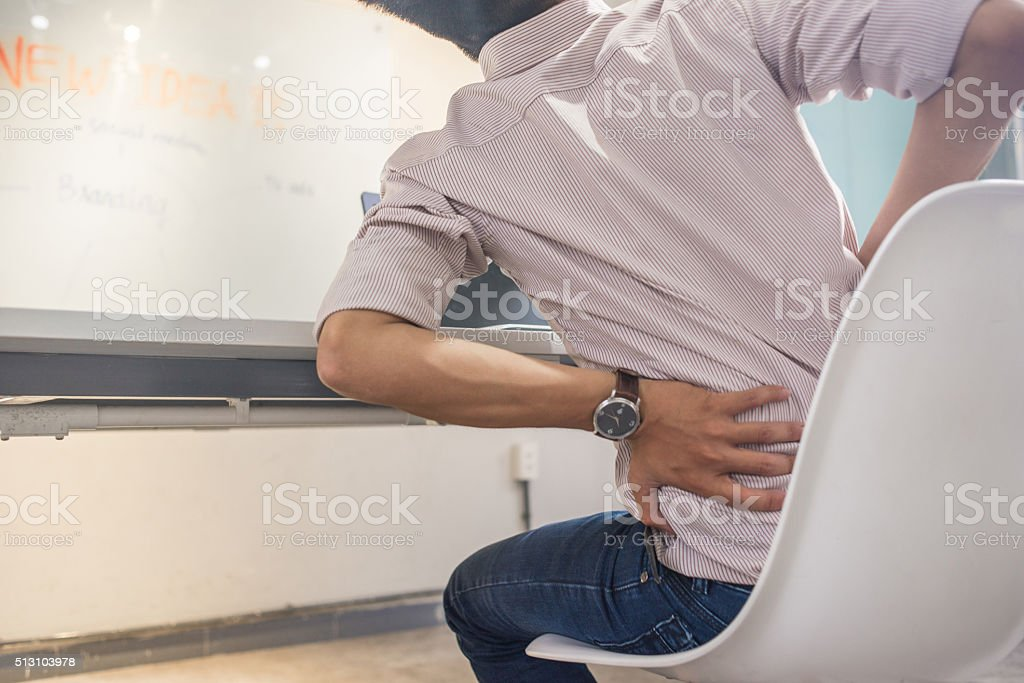 Backache-popular symptom of office worker after long time sitting stock photo