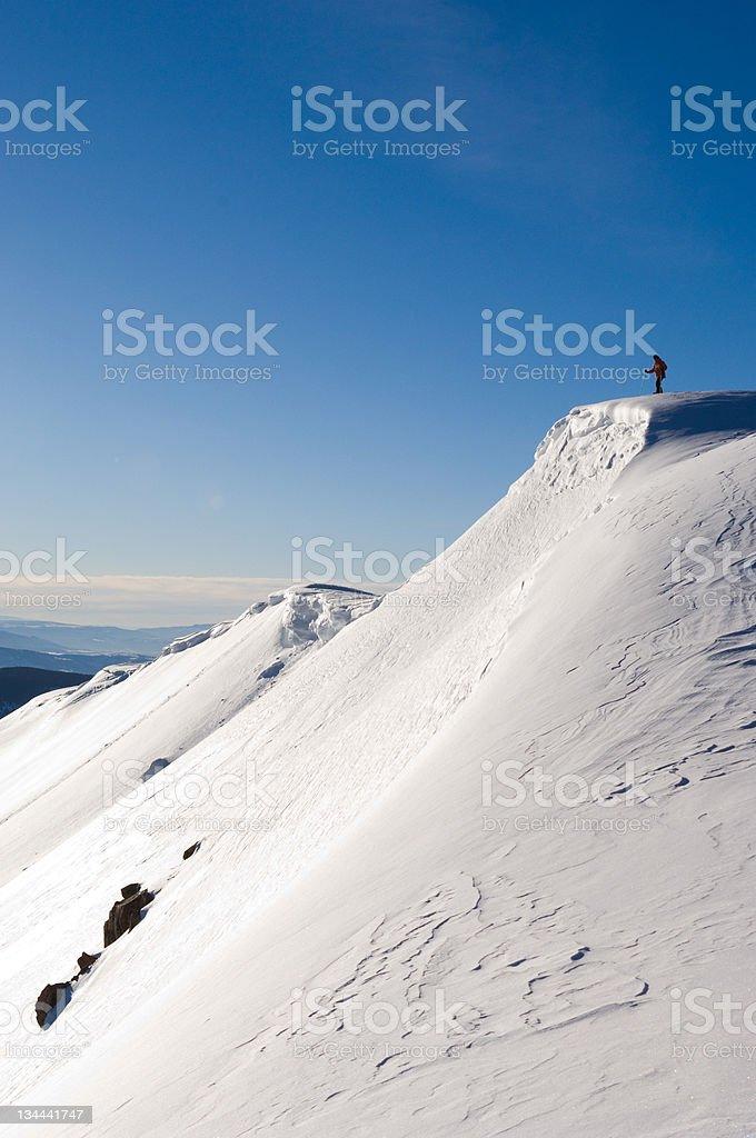Backcountry Skier Mountaineer Standing on Corniced Mountain Ridge stock photo