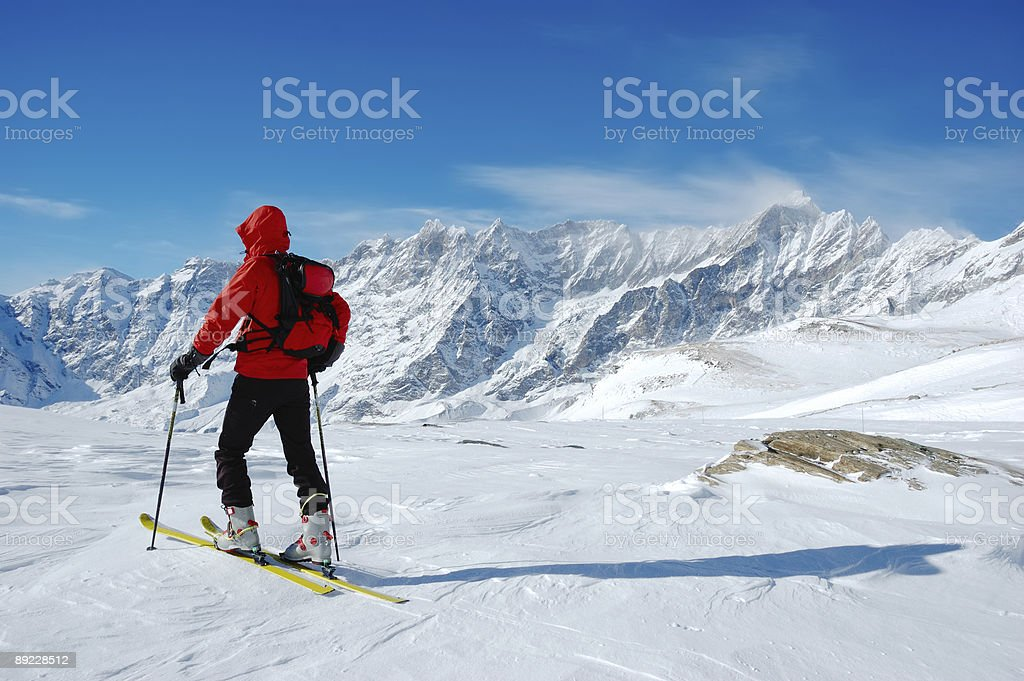 Backcountry skier with snowy mountain peaks as a backdrop royalty-free stock photo