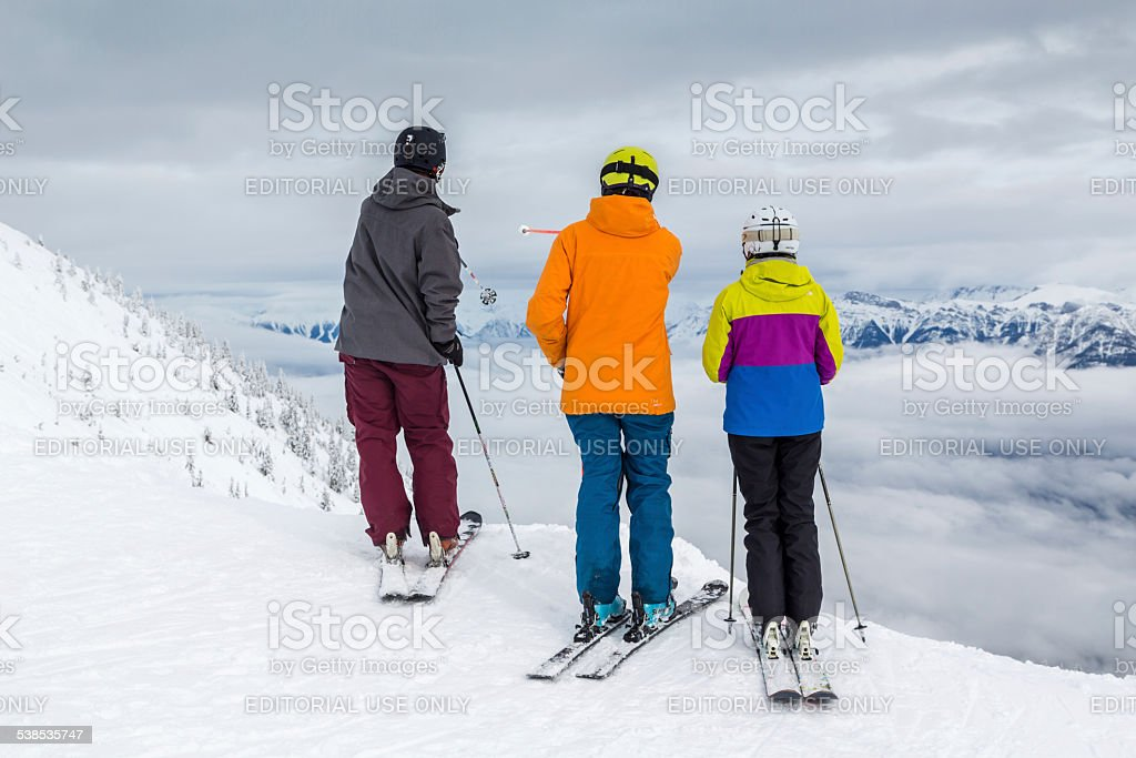 Backcountry Skiers at Mountain Summit Looking at View stock photo