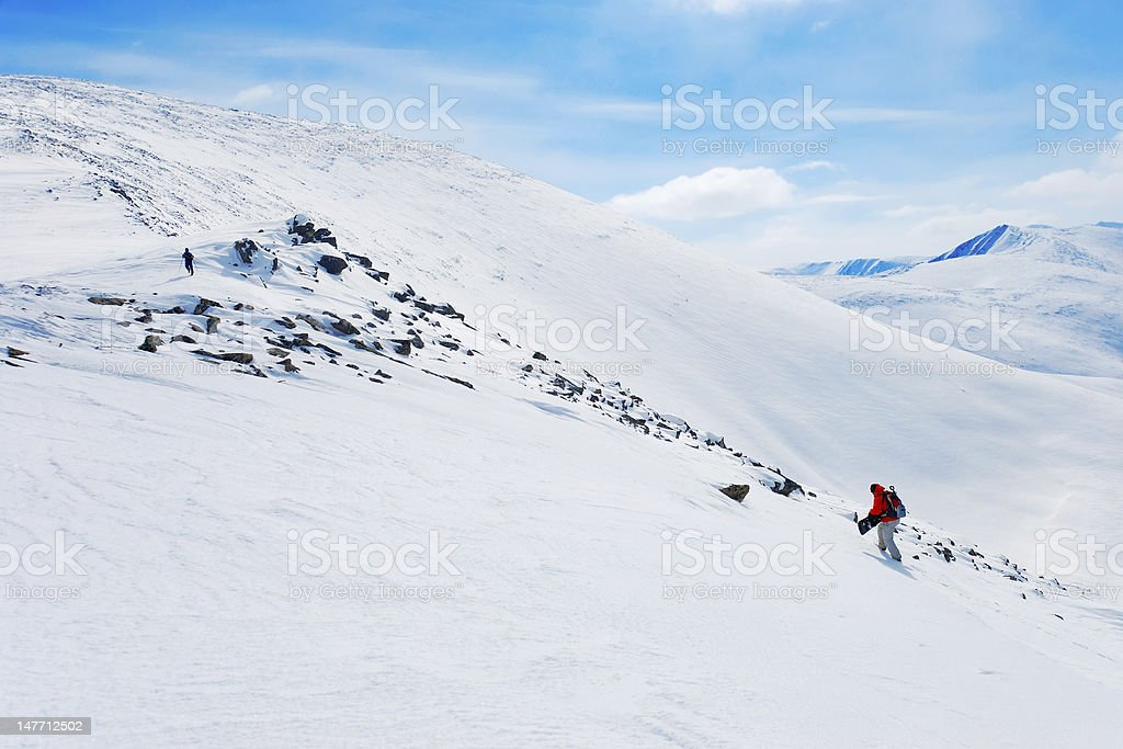 Backcountry snowboarder climbing up royalty-free stock photo