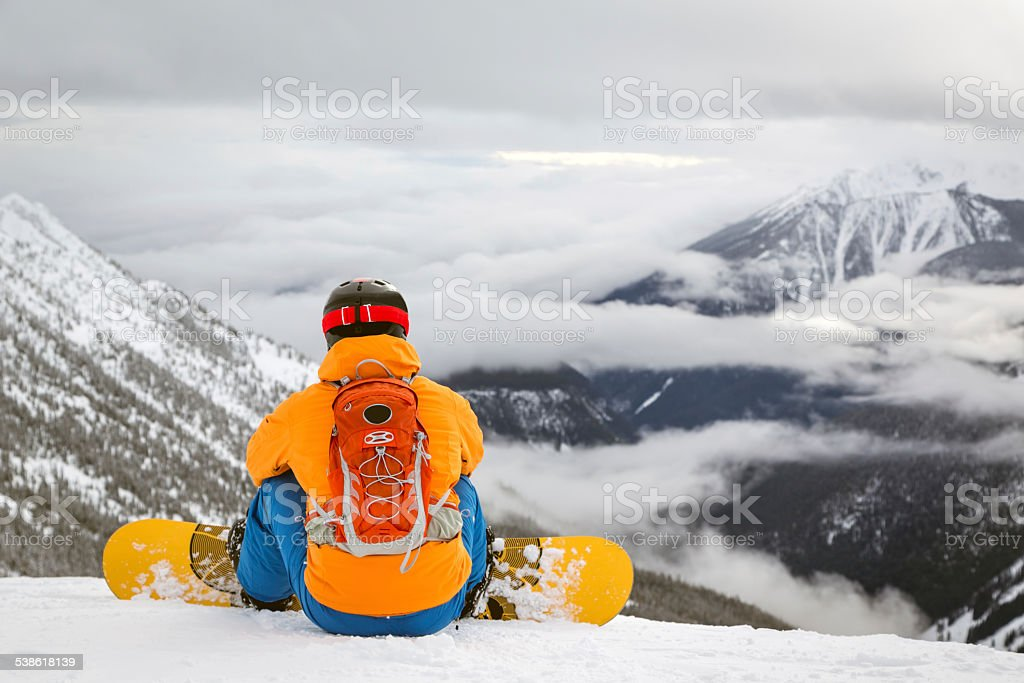 Backcountry snowboarder on Mountain Summit and looking at the cliff stock photo