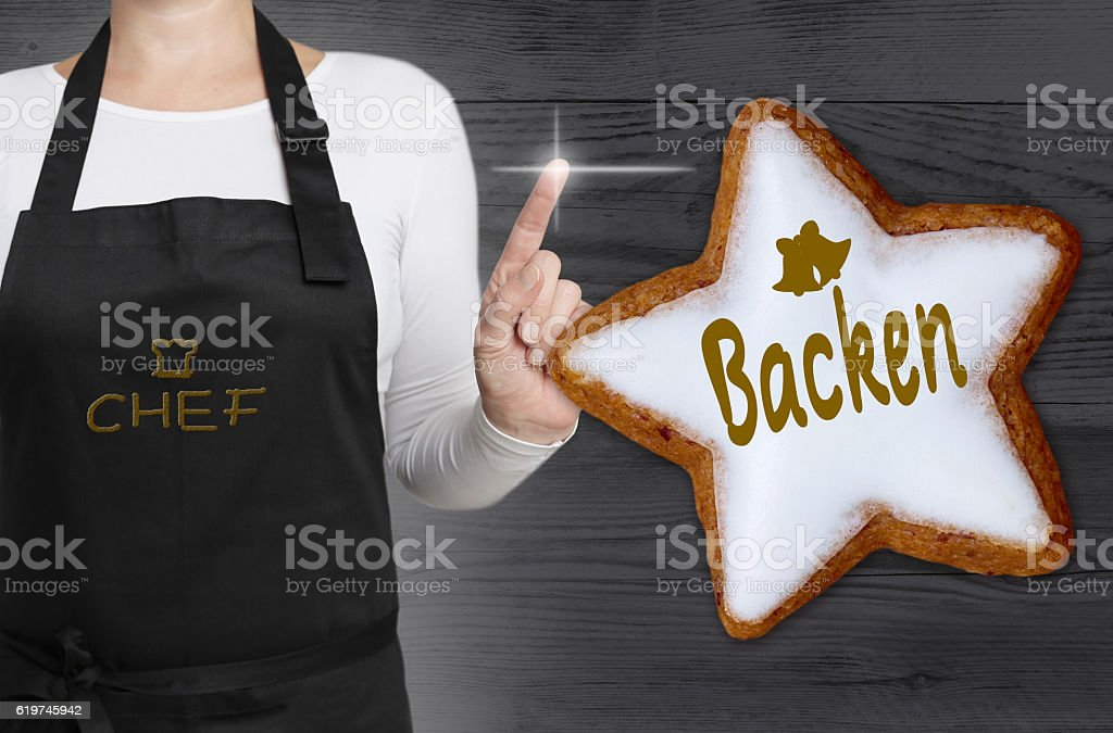 Backen (in german baking) cinnamon star is shown by chef stock photo