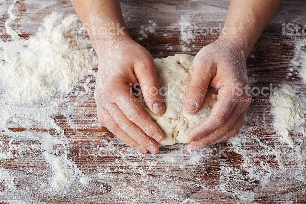 Backer kneading the dough with flour for bread or pizza stock photo