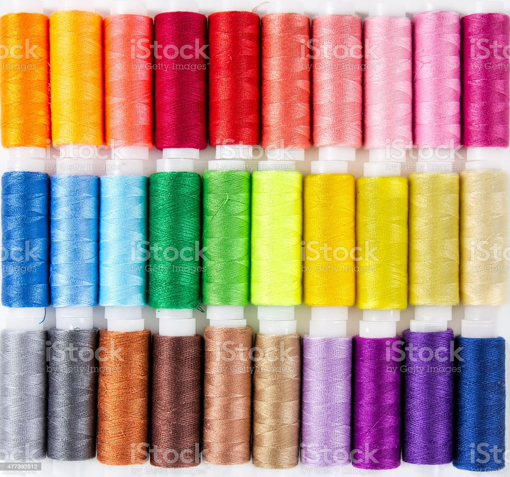 Background from bobbins with multicolored thread stock photo