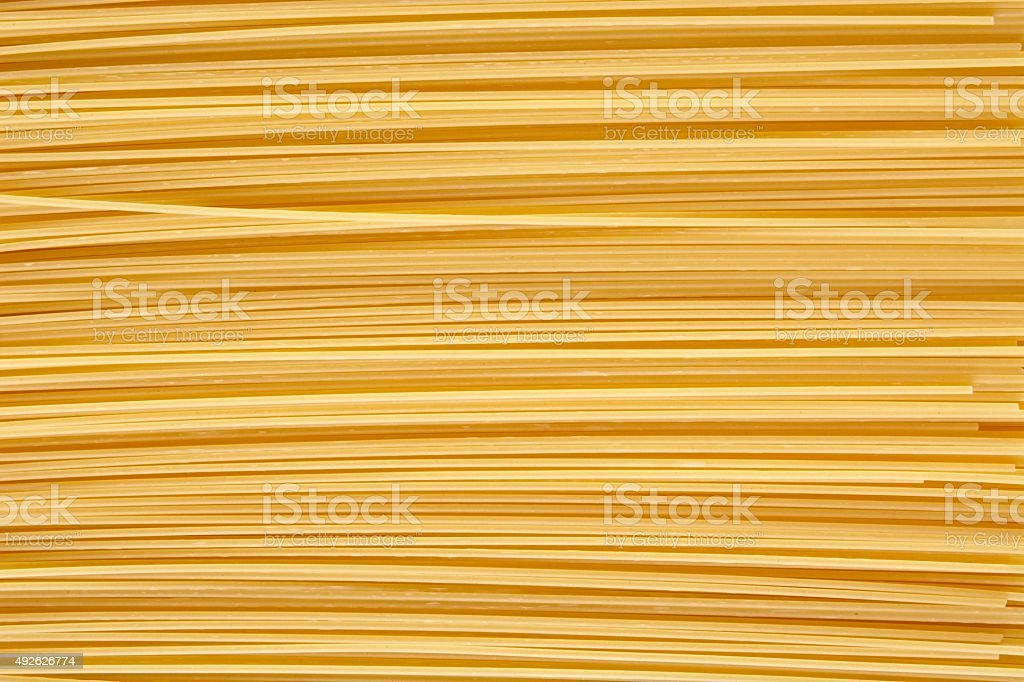 Background made of raw pasta stacked horizontally stock photo