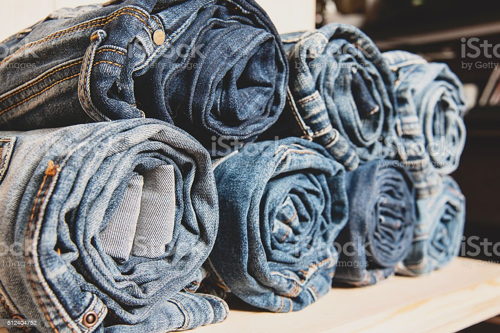 background of a stack rolled jeans on shelf stock photo