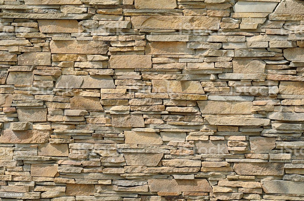Background of a stone wall cladding texture, brown stone bricks stock photo